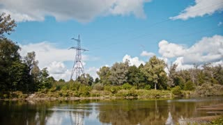 Wide shot timelapse of electricity power lines and high voltage pylons on a field in the countryside at summer near river