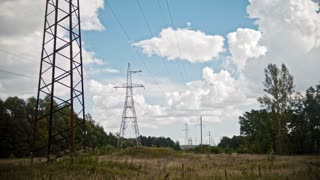 Wide shot timelapse of electricity power lines and high voltage pylons on a field in the countryside at summer.