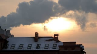 Winter cold sunset above city buildings roof