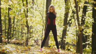 Woman doing fitness exercises outdoor. Female stretching her loin in autumn forest. Slim girl at outdoor workout