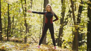 Woman doing fitness exercises outdoor. Female stretching her shoulders in autumn forest. Slim girl at outdoor workout