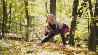 Woman doing fitness exercises outdoor. Female stretching in autumn forest. Slim girl at outdoor workout - squats