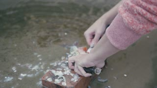 Woman near river cleans fish with knife, outdoor, close up
