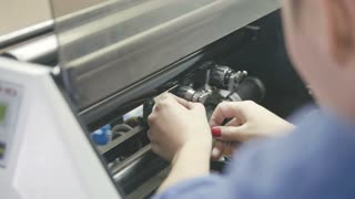 Woman with red nails repair the printing machine, polygraph industry