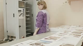 Woman working with touch screen on polygraph folder machine in printing house
