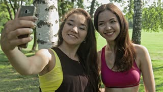Women taking selfies after fitness exercises in the park