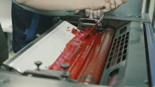 Worker at Polygraphy printing industry use Red paint on ink roller, close up