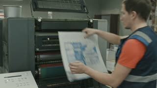 Worker pulls on the blank printable on polygraph industry process, color printing
