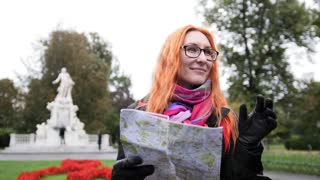 Yong woman tourist with red hair adjusts her glasses and looking map in Burggarten, Vienna, Austria
