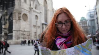 Yong woman tourist with red hair and glasses looking map in Vienna and looks around in an unfamiliar city near Stephansplatz, Austria