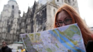Yong woman tourist with red hair and glasses looking map in Vienna near Stephansplatz, Austria