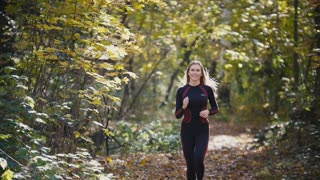 Young active female athlete exercising outdoor autumn park. Girl smiling, hair waving, Healthy women, slow-motion