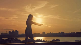 Young attractive girl with flowing hair dancing acrobatic moves at sunset silhouette