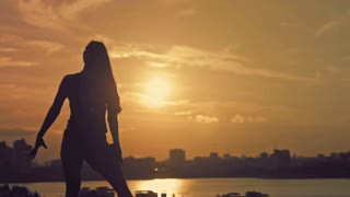 Young attractive girl with flowing hair dancing at sunset silhouette