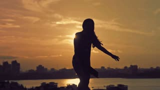 Young attractive girl with flowing hair dancing movements of Kupwara at sunset silhouette