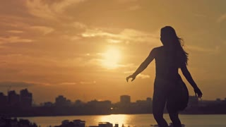 Young attractive girl with flowing hair dancing pirouettes at sunset silhouette