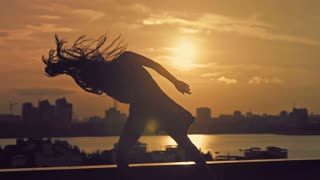 Young attractive girl with flowing hair doing the dance moves at sunset silhouette