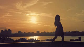 Young attractive girl with flowing hair over the sun dancing the movement of ballet at sunset silhouette