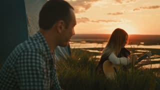 Young attractive girl with friends plays acoustic guitar in camping outdoors on high hill at summer sunset