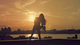 Young attractive girl with sun shines through flowing hair dancing the movement of ballet at sunset silhouette