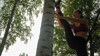 Young attractive sport woman doing stretching exercises near the birch in the park over the sun, dolly shot