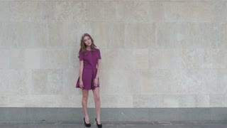 Young attractive woman posing near wall for fashion photographer