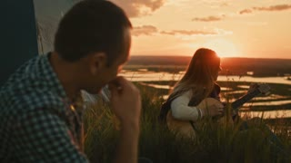 Young attractive woman with friends tunes acoustic guitar in camping outdoors on high hill at summer sunset