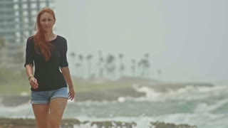 Young attractive woman with long red hair dressed in short shorts walking along the storm sea, slow-motion