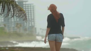 Young attractive woman with long red hair dressed in short shorts walking at the coast opposite the storming sea, move away, slow-motion