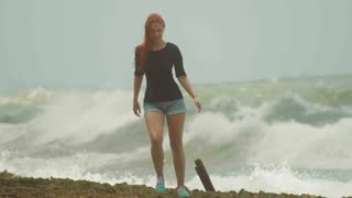 Young attractive woman with long red hair dressed in short shorts walking at the coast opposite the storming sea, slow-motion