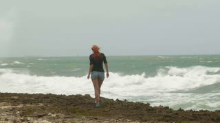 Young attractive woman with long red hair dressed in short shorts walking at the coast opposite the storming sea