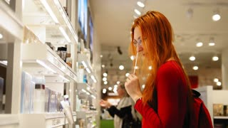 Young attractive woman with red hair choosing a perfume in duty free area at airport