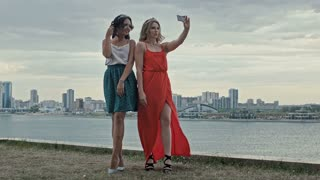 Young beautiful girls having fun and making selfie on high hill over the city