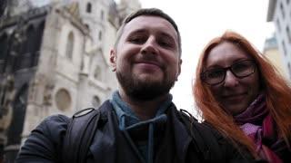 Young couple european beard man and red hair female makes a selfie near Stephansplatz in Vienna, Austria, rainy autumn