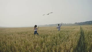 Young couple - man and woman running with kite in field