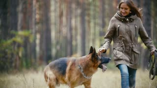 Young cute happy woman plays with her dog - german shepherd in yellow autumn park, slow-motion