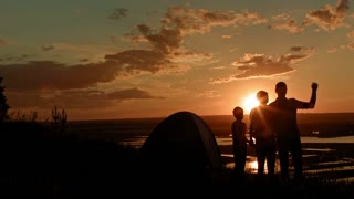 Young family - dad mom and son in camping - stands on high hill at summer sunset and have happy, silhouette