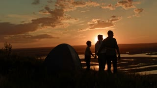 Young family - father, mother and son in camping - stands on high hill at summer sunset, looking for landscape, silhouette