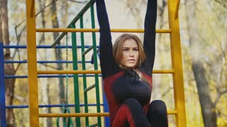 Young fitness female model Exercising in a Meadow at autumn park, Sports Outdoor Activities concept - exercises on the horizontal bar, front view