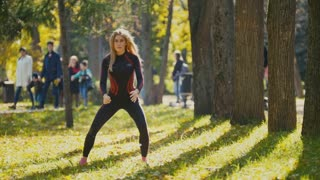 Young fitness female model Exercising in a Meadow at autumn park, Sports Outdoor Activities concept - squats