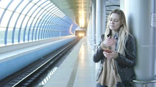 Young girl with gadget long blonde hair in leather jacket with straightens hair standing in metro against the background of a train coming