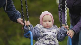 Young happy family at playground - dad, mother and laughing baby daughter - children's swing, close up