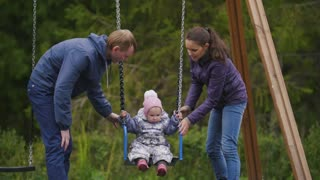Young happy family at playground - dad, mother and laughing baby daughter - children's swing