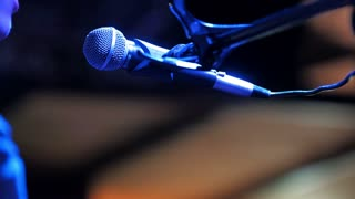 Young man sings to microphone in night club, close up