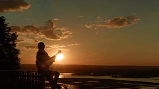 Young romantic woman playing the acoustic guitar, at sunset near camping on high hill, silhouette, wide angle