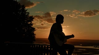 Young romantic woman playing the acoustic guitar, at sunset near camping on high hill, silhouette
