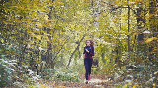 Young runner girl have jogging on autumn road covered with fallen leaves. Sports healthy lifestyle concept, slow motion