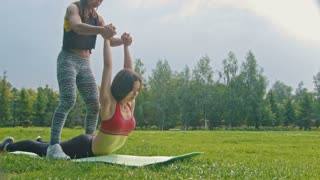 Young sport women doing stretching exercises for the spine in the park, dolly shot