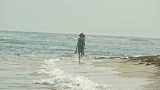Young woman In long Dress hold a hat and Walking along the sea at the water's edge, slow-motion