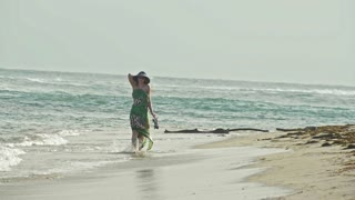 Young woman In long Dress hold a hat and Walking along the sea, slow-motion